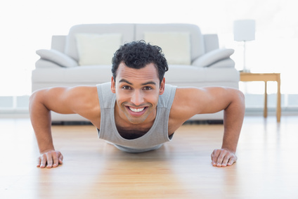 Portrait of a sporty smiling young man doing push ups in the living room at house